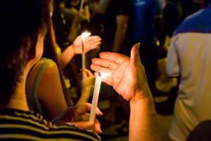 community in mourning holding lit candlesticks