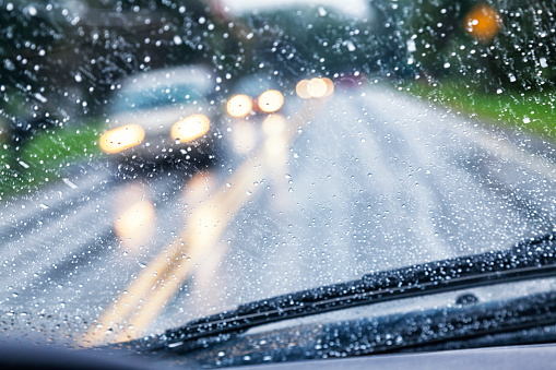 Driver POV (point of view) looking over the windshield wipers through the wet, blurry, partially opaque, partially transparent, spot speckled windshield of a car traveling on a rural highway during an autumn rain storm. Hazy, blurred headlights of approaching vehicle traffic are just blobs of light through the streaking and splattered raindrop water.